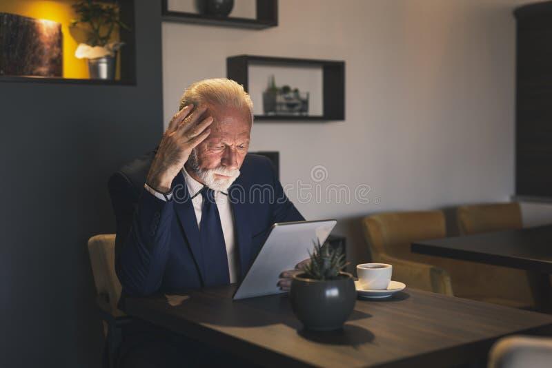 Старший бизнесмен работая на планшете стоковые изображения