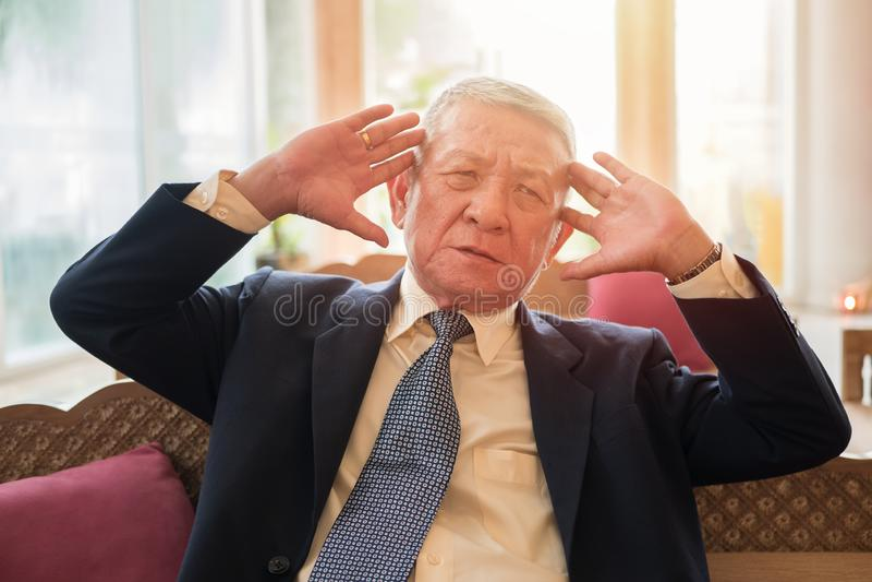 Старший бизнесмен управляющего директора страдая от головной боли от проблемы работы дела на рабочем месте офиса здравоохранение, стоковые фото