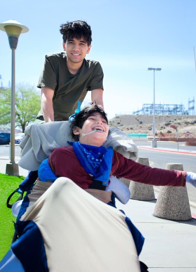 Старший брат нажимая счастливого неработающего мальчика в кресло-коляске стоковое изображение rf