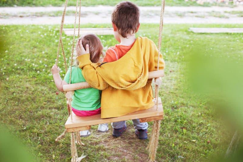 Старший брат обнимая маленькую сестру стоковая фотография rf