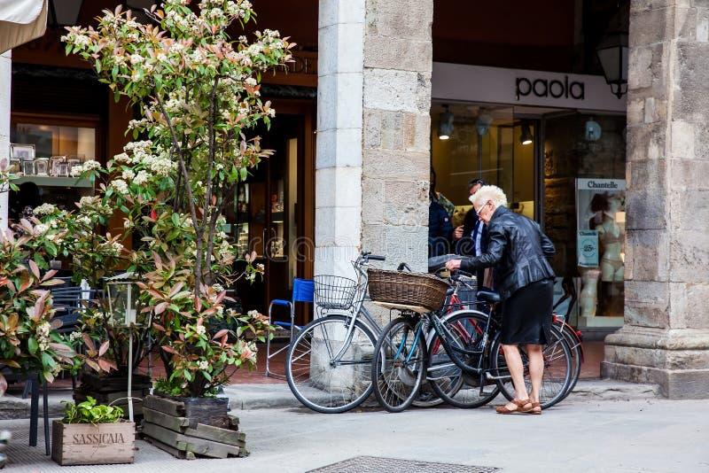 Старший велосипедист дамы в центре города Пизы стоковые фотографии rf