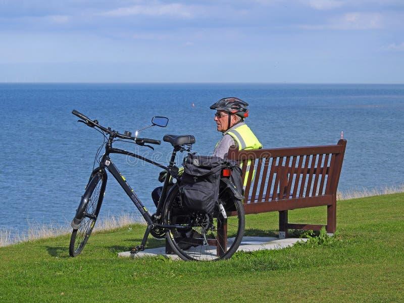 Старший велосипедист на прибрежном стенде стоковое фото