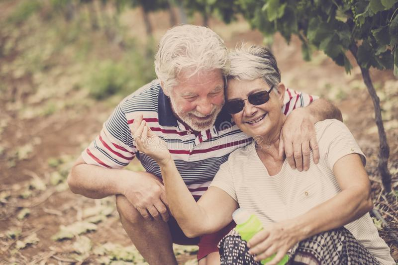 Старший взрослый смех пар в happines совместно навсегда играя с пузырями мыла в досуге двора страны на открытом воздухе стоковая фотография