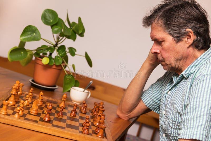 Старший взрослый играет шахмат стоковые фото
