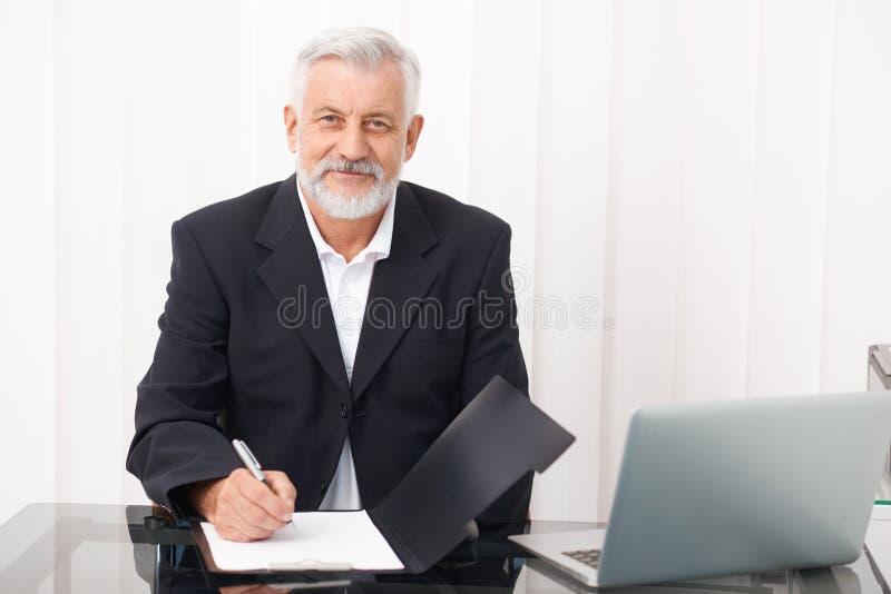 Старший врач усмехаясь и смотря в камеру стоковое изображение rf