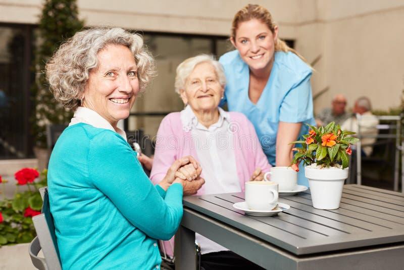 Старший гражданин пьет кофе с визитом и ухаживающим за больными стоковые фотографии rf