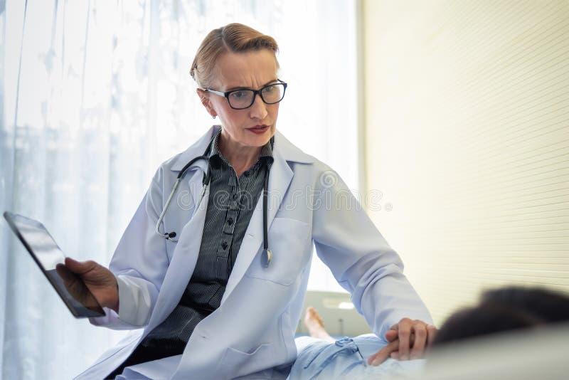 Старший доктор женщины успокаивая ее женский пациента стоковое фото