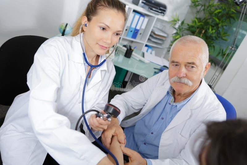 Старший доктор и молодая женщина internist проверяя кровяное давление пациентов стоковое изображение