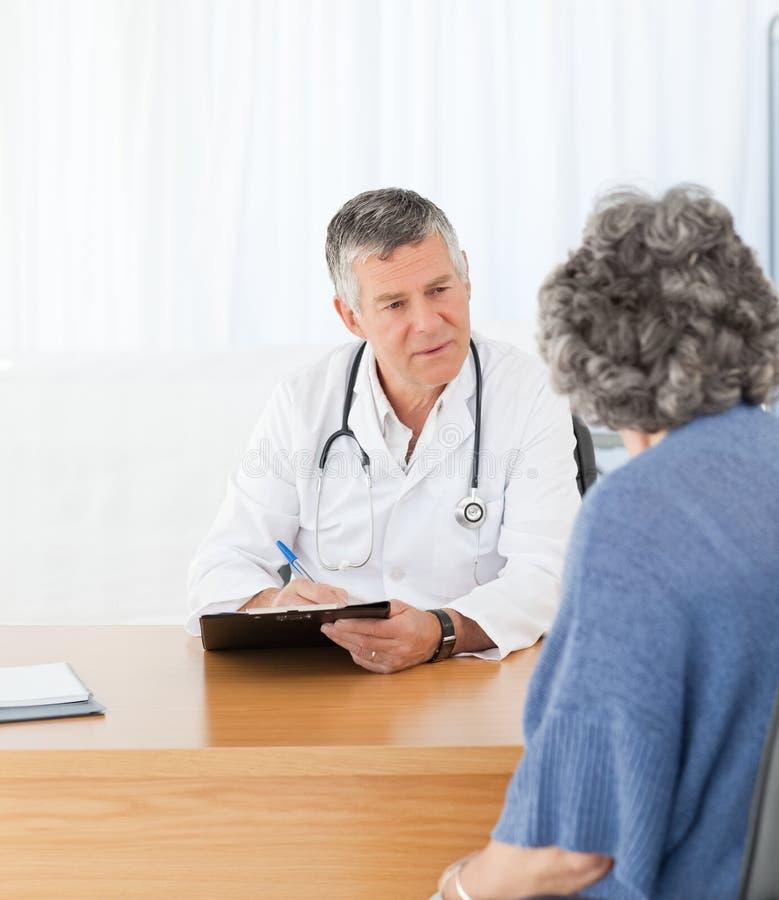 Старший доктор разговаривая с его пациентом стоковое изображение rf