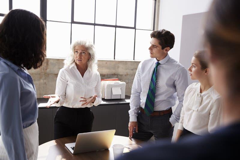 Старший женский менеджер адресуя команду в деловой встрече стоковая фотография rf