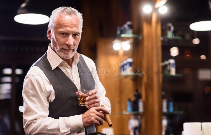 Старший джентльмен с стеклом и сигарой стоковое изображение rf