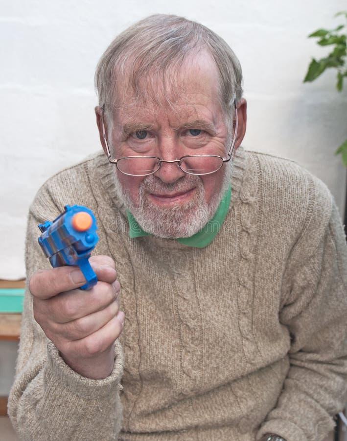 Старший играть с пушкой игрушки стоковое изображение