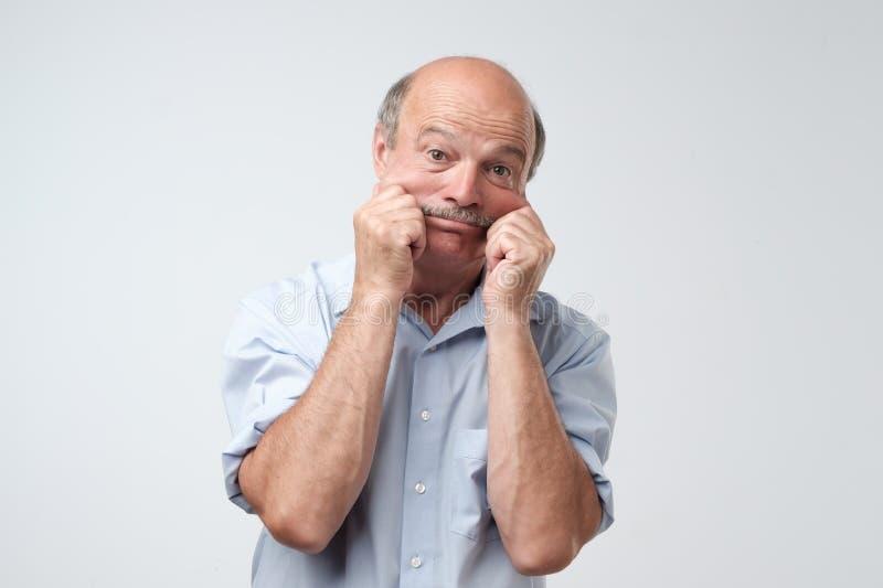 Старший испанский человек в голубой рубашке вытягивая кожу на стороне с руками Он вспугнут или утомлян стресса стоковые изображения