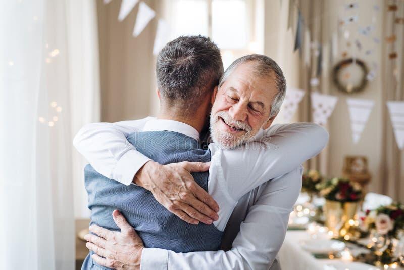 Старший и зрелый человек стоя внутри помещения в наборе комнаты для партии, обнимая стоковые изображения