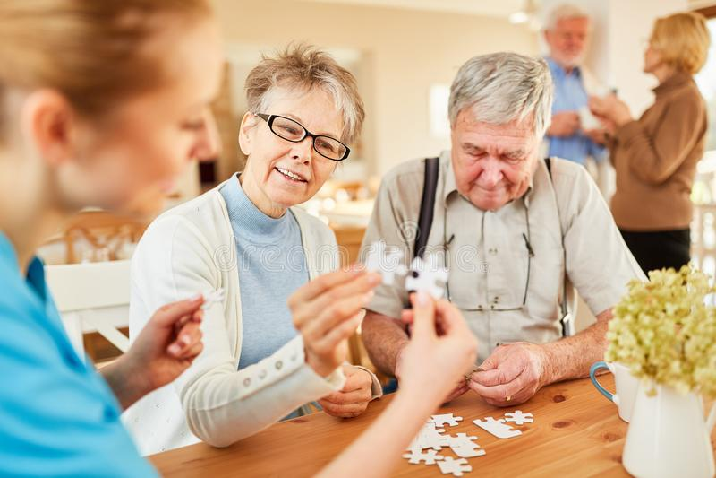 Старший и geriatrician играя головоломку стоковая фотография