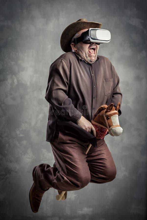 Старший кавказский взрослый человек наслаждается испытать immersive имитацию игры ковбоя виртуальной реальности Концепция портрет стоковое фото rf