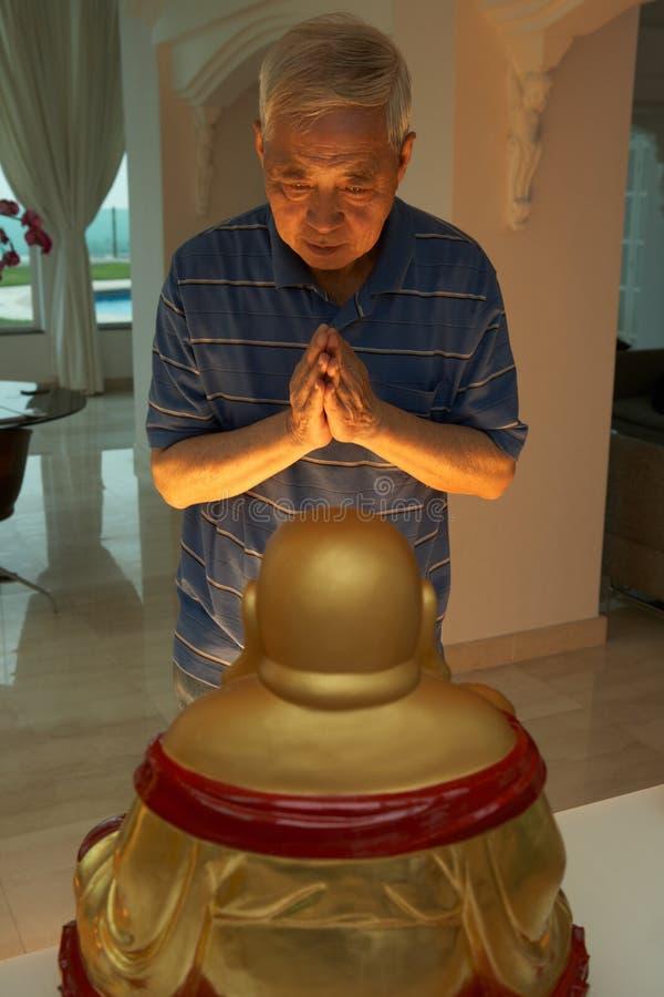 Старший китайский человек моля к статуе Будды стоковое фото rf
