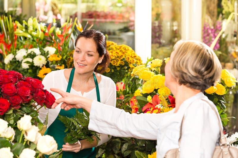 Старший клиент покупая красные розы магазином цветка стоковое изображение rf