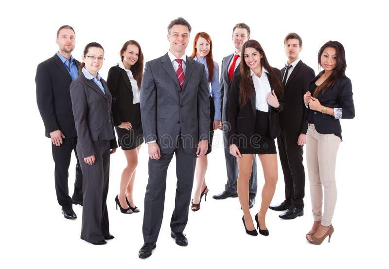 Старший коммерческий директор стоя на фронте его команды стоковое изображение rf