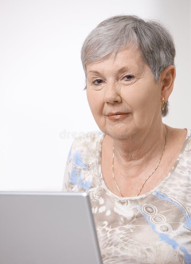 старший компьтер-книжки компьютера используя женщину стоковые фотографии rf
