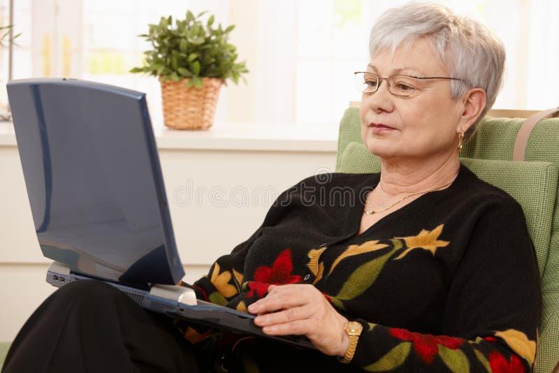 старший компьтер-книжки компьютера используя женщину стоковая фотография rf