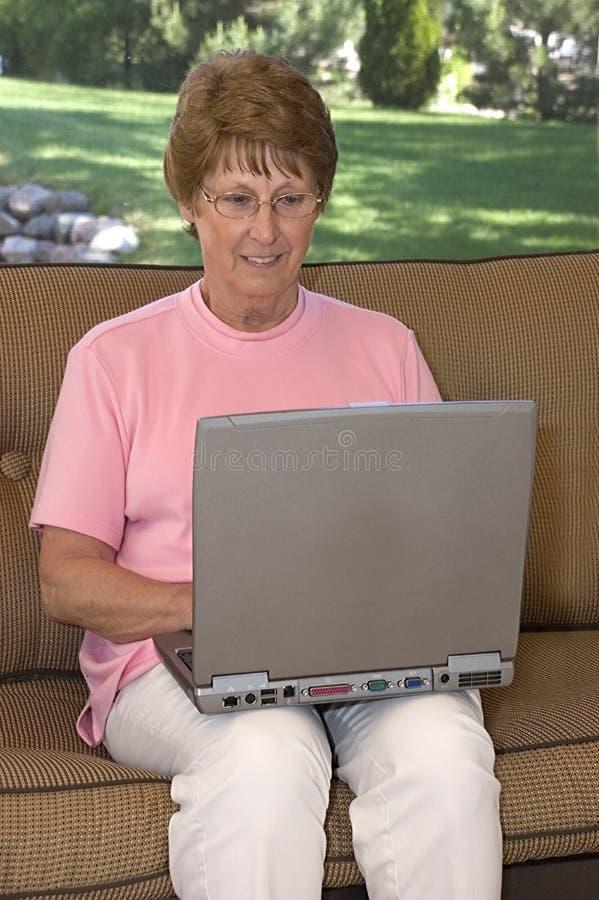старший компьтер-книжки компьютера используя женщину стоковое фото