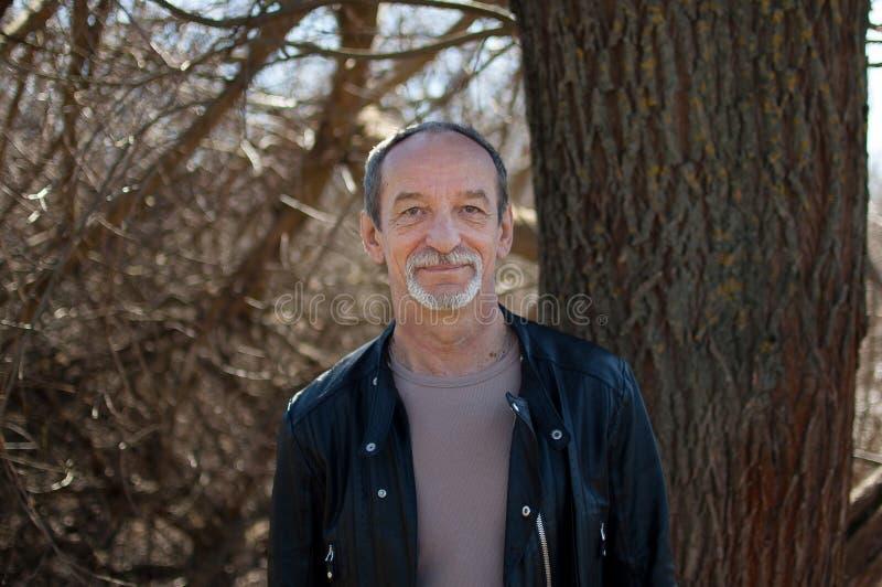 Старший красивый человек нося темную кожаную куртку стоя outdoors около дерева на предпосылке голубого неба стоковые изображения rf
