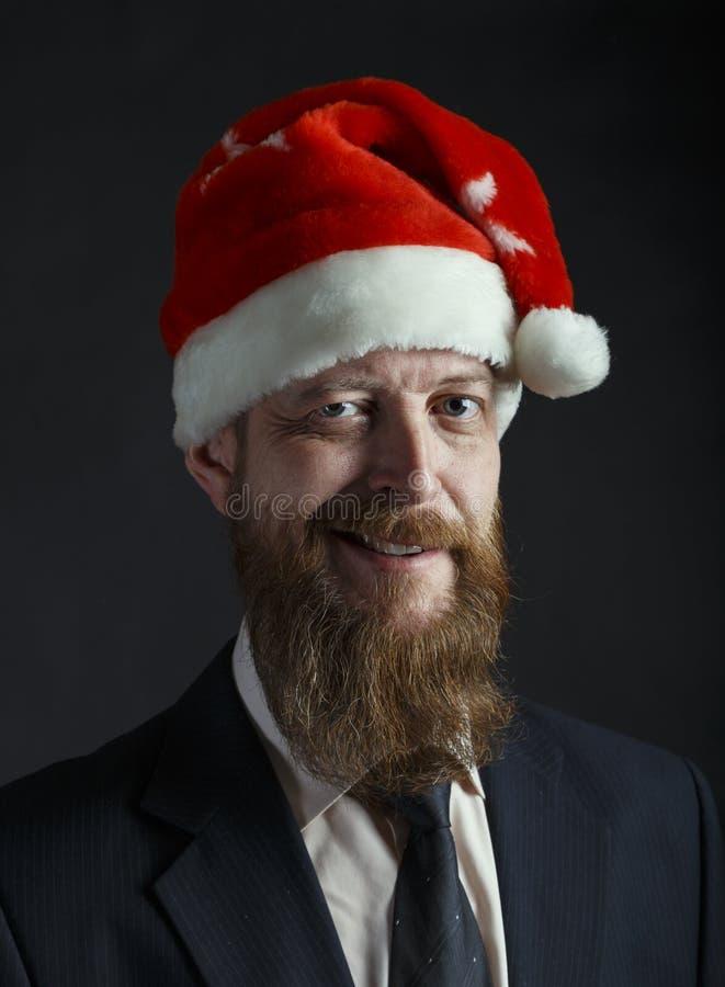 Старший красный бородатый бизнесмен со смешной улыбкой в шляпе santa на черной предпосылке стоковое фото