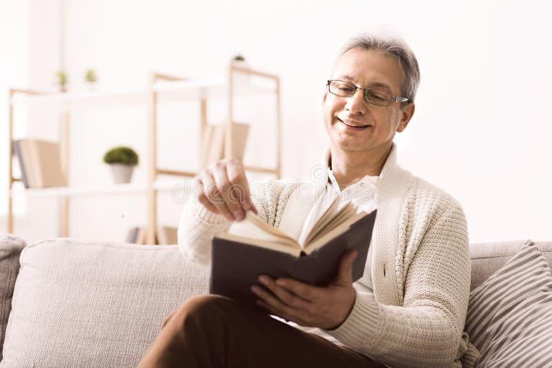 Старший мужчина в очках наслаждается хорошей книгой с улыбкой стоковые изображения