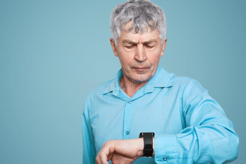 Старший мужчина с серьезным выражением смотрит smartwatch с применением здоровья, контролирует его положение, подсчитывает калори стоковые изображения