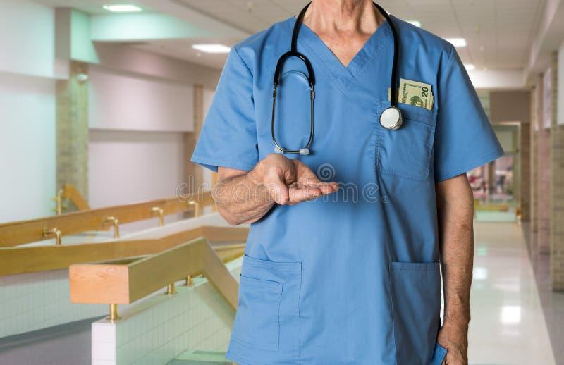 Старший доктор внутри scrubs просить оплата стоковая фотография