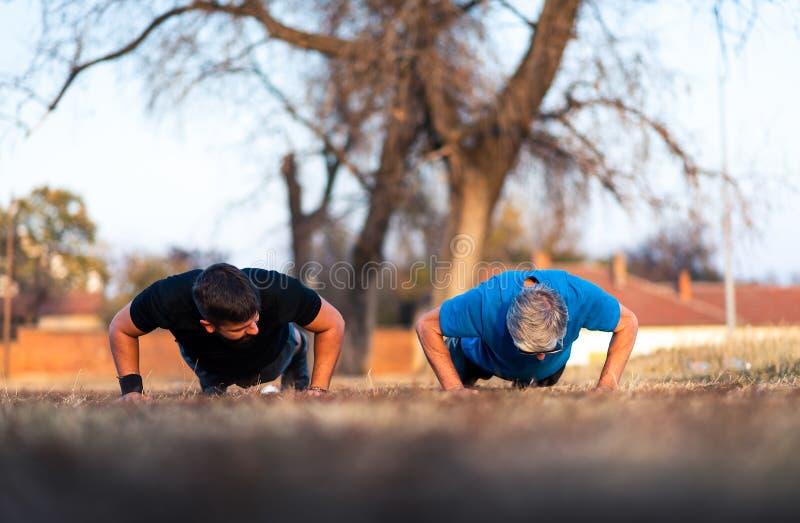 Старший отец и сын делая pushups outdoors стоковые изображения