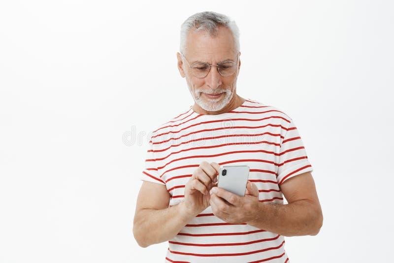 Старший отец проверяя если дети alright писать сообщение через стекла смартфона нося пока печатающ на экране мобильного телефона стоковые фотографии rf