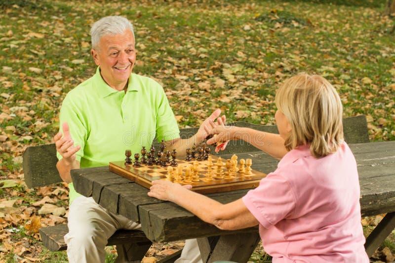старший пар шахмат счастливый играя стоковое изображение