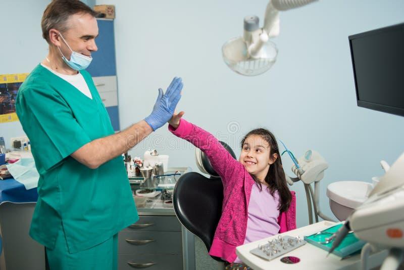 Старший педиатрический дантист и счастливая девушка после обрабатывать зубы на зубоврачебном офисе клиники, усмехаться и давать в стоковое фото rf