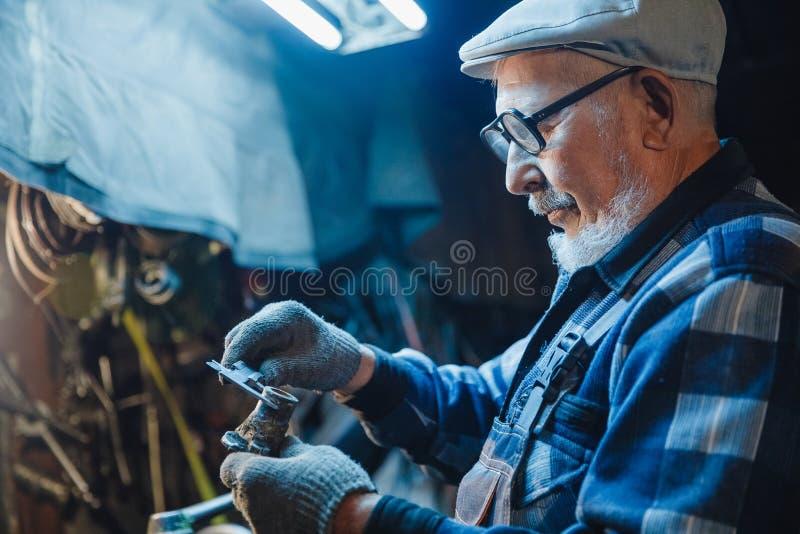Старший пожилой мужской механик тернера работая на механическом инструменте для металла Дизайн концепции промышленный стоковое изображение