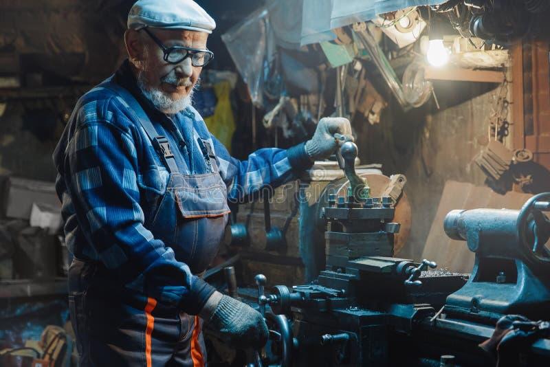 Старший пожилой мужской тернер регулирует металл на машине Работник промышленный, рабочее место пенсии концепции стоковая фотография rf