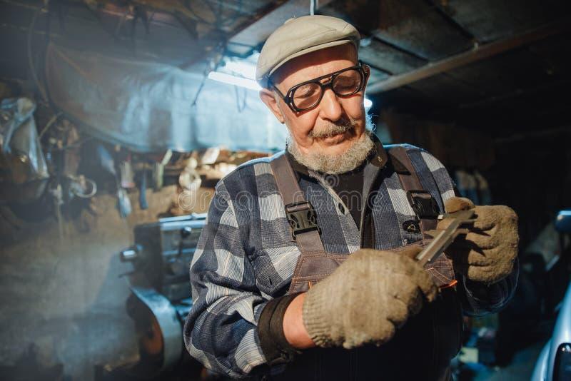 Старший пожилой мужской тернер регулирует металл на машине Работник промышленный, рабочее место пенсии концепции стоковые фото