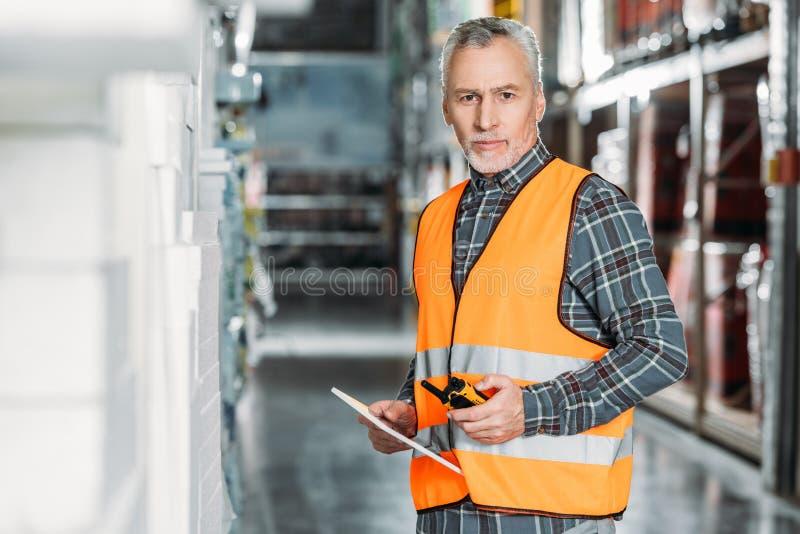 старший работник в жилете безопасности используя цифровое звуковое кино планшета и walkie стоковые изображения