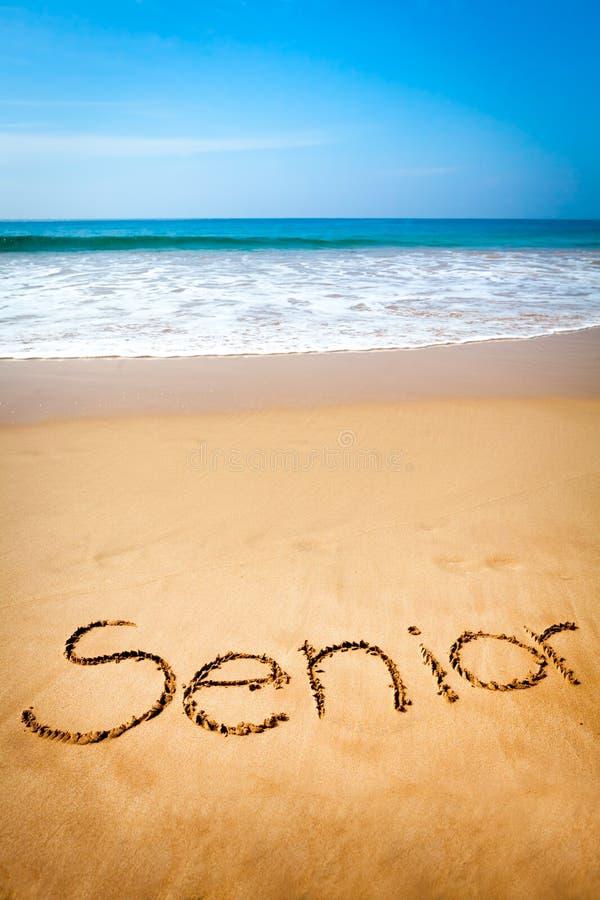 Старший слова написанный в песке, на тропическом пляже стоковые фото
