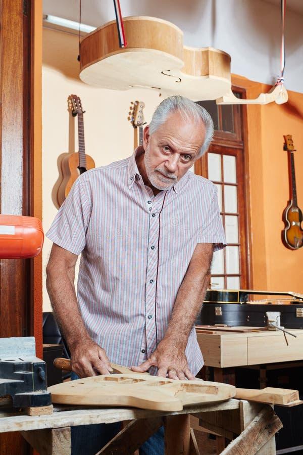 Старший создатель гитары работая с древесиной стоковая фотография