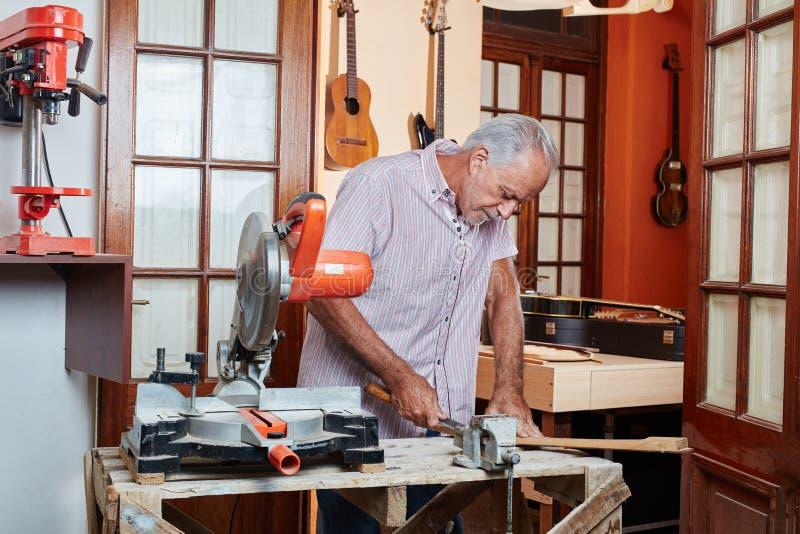 Старший создатель гитары работает с концентрацией стоковые изображения