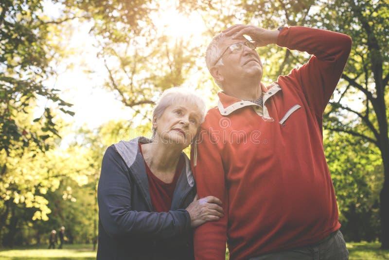 Старший стоять пар утомлял в парке после тренировки стоковая фотография