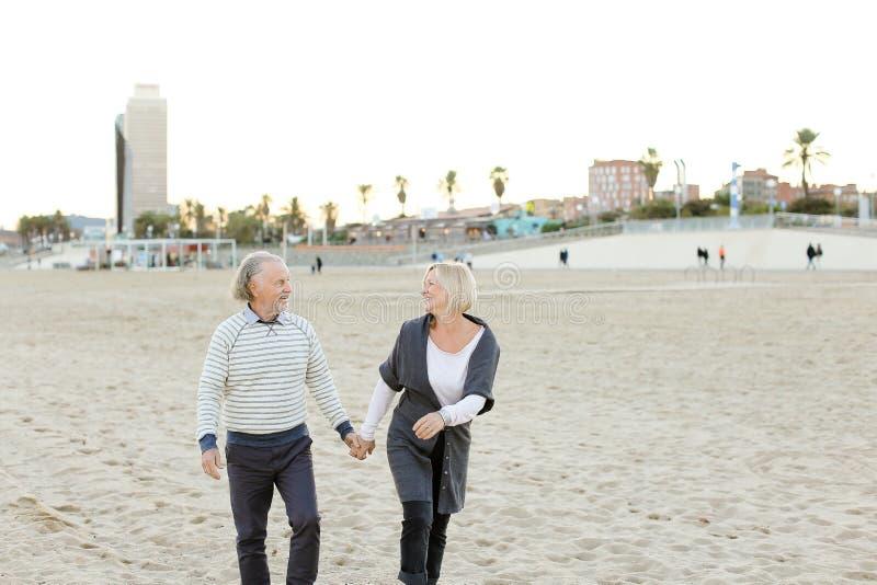 Старший супруг и усмехаясь жена бежать на пляже песка и держа руки стоковые изображения rf