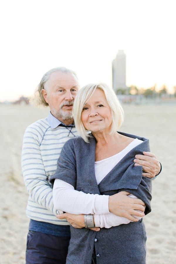 Старший супруг обнимая кавказскую жену в предпосылке пляжа песка стоковое изображение rf