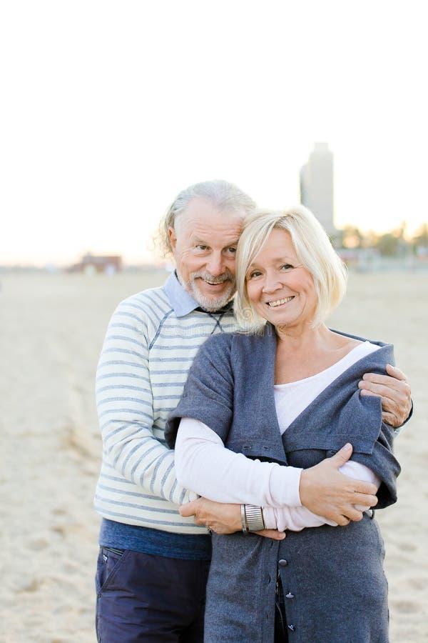 Старший супруг обнимая счастливую жену в предпосылке пляжа песка стоковое изображение rf