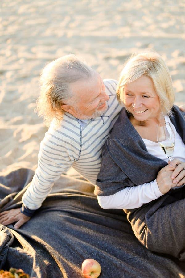 Старший супруг обнимая усмехаясь жену сидя на шотландке с шампанским на пляже песка стоковые фотографии rf
