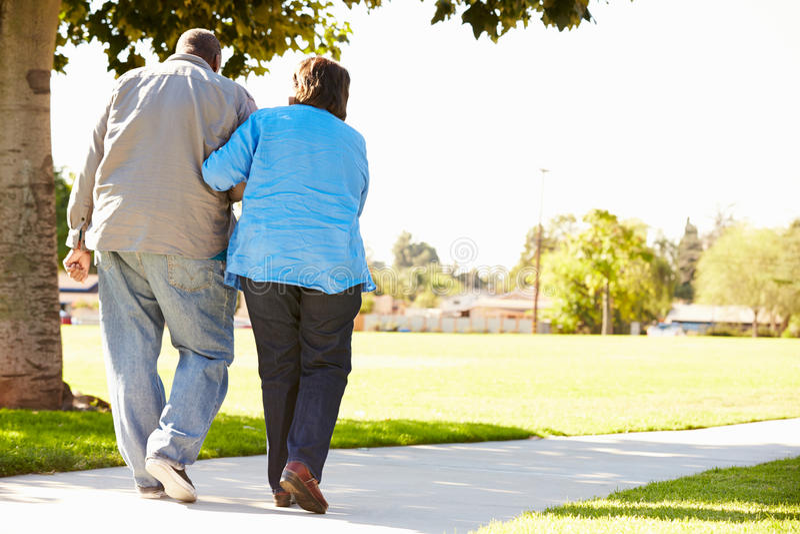 Старший супруг порции женщины по мере того как они идут в парк совместно стоковые изображения