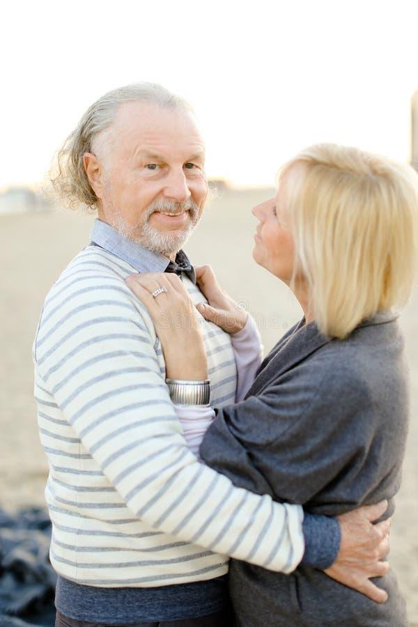 Старший усмехаясь супруг обнимая жену в предпосылке пляжа песка стоковые изображения