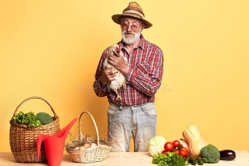 Старший фермер пришел выйти на рынок со свежими овощами и яйцами от его фермы стоковые фотографии rf